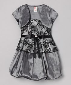 Fashion-focused little ones will feel at once girly and glamorous dressed in this glossy set. The bow-topped sash, poufy silhouette and matching shrug combine to give it the perfect blend of tasteful and stylish appeal.