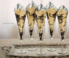 Be fancy and serve popcorn in cones - just take clear plastic craft paper (you can find at craft stores with scrapbook paper) and roll into a cone - use double sided tape to hold close! Put them in wine glasses or a decorated box to help them stand up straight!