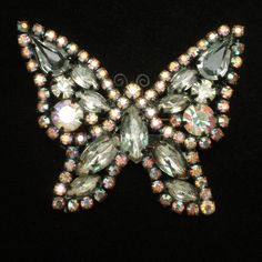 "Pretty butterfly with sparkly rhinestones set in black japanned metal. This butterfly pin is in good to very good condition. It is hallmarked Weiss on the reverse. The butterfly measures 1 3/8"" x 2"""