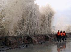 Paramilitary policemen patrol as waves crash against dikes at Dongtou
