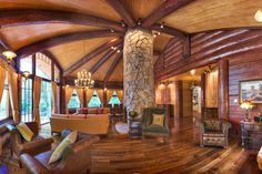 Once low-slung, dark cabins, these days log homes are open and even have curved contemporary architecture, like this great room designed by Mr. Arnott on the home in the Catskills.