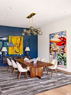 The dining room balances the bright yellow foreground of a mixed-media work with the cool blue lacquered finish of the wall on which it's displayed.