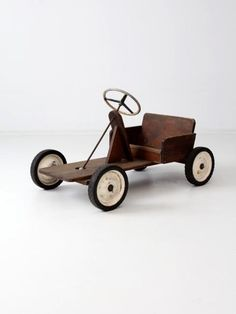 """A vintage toy riding car. The large wooden car """"cart"""" has a metal frame with wood seating. The front wheels move with the wheel. riding toy car wood with metal CONDITION In good condition with wear consistent with age and use. MEASUREMENTS Length 39.5 inch 100.3 cm Width 21.5 inch 54.6 cm Height 22 inch 55.9 cm Seat Height 9.5 inch 24.1 cm Seat Width 17.5 inch 44.5 cm Please review our shipping information."""