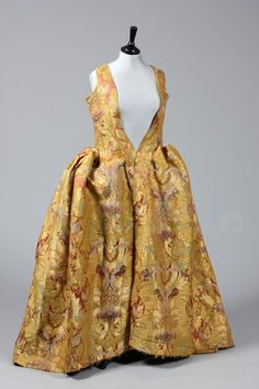 the remains of a luxurious gold brocaded lampas robe à la Française, mid 18th century, the silk circa 1730-40 with large-scale design of foliate palmettes in predominantly gold with deep salmon satin and lime brocade highlights, comprising: complete back and front sections, unpicked and re-sewn hip sections, but lacking sleeves.