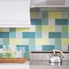 Glass Block Backsplash. This backsplash is both stylish and eco-friendly. The tiles were created from glass that would have otherwise ended up in a landfill. A random arrangement of blue, yellow, and green tiles adds visual energy to the room and provides a dramatic pop of color to the kitchen's predominantly neutral hues.I would replace the blue