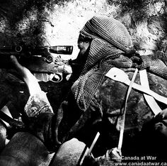 Private L.V. Hughes, 48th Highlanders of Canada, sniping German position, near Foglio River, Italy, 1944.