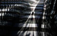 A man walks between glass facades of the Bonn Post Tower, the headquarters of German postal and logistics group Deutsche Post DHL in Bonn on March 5, 2013.  Photo by Wolfgang Rattay/Reuters