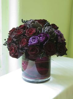 Dark burgundy rose, purple lisianthus, artichoke and burgundy aspidistra arrangement.