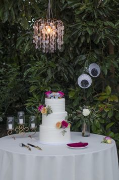 Wedding Cake Table decorated with Flowers below our Vintage Chandelier. Nick Charrow Photography.