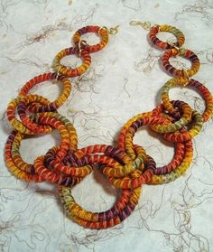 Bold ~ lightweight ~ colorful ~ soft ~ fun2wear!    Beautiful silk ribbon wraps aroung rings to create an attention getting necklace. The intense colors- orange, pumpkin, copper, gold, sage - are of silk sari recycled into ribbon made by a womens co-operative in Nepal. This necklace gets attention.    21 in length; 3 different sized rings- . Gold plated hook & eye closure.    Shipping is USPS First Class boxed, if you prefer Priority Mail please contact me.