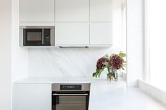 Modern kitchen by Studio Mills. Pale green cabinets and white marble worktops