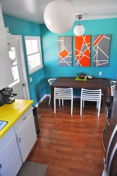 those paintings look like they could be a relatively easy DIY job w/ some canvases and painter's tape....not to mention the orange and grey look awesome against the turquoise