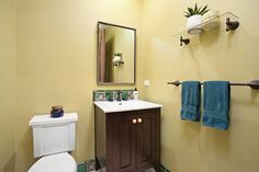 Soft yellow walls are punctuated by Mediterranean tiles in this sweet and simple powder room.