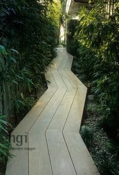 Zag wooden decking path between boundary wall and house. Pebbles and cobbles create a mulch to mimic a dry river bed. Bamboo screening.   Harpur Garden Library