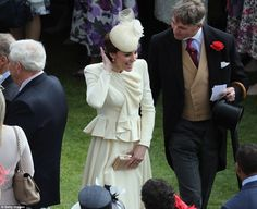 Kate made sure her coiffed updo  stayed in place with a quick check on her hairstyle...