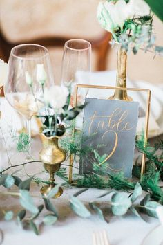 Rather than completely imitating the era, this reception table intertwines its elements into a subtle, contemporary style. Brass candlesticks, simple and elegant table numbers in a gilded frame, and foliage nestle together for a beautiful centerpiece. Green Wedding Centerpieces, Wedding Table Centerpieces, Wedding Table Settings, Wedding Table Numbers, Ceremony Decorations, Flower Centerpieces, Centerpiece Ideas, Candlestick Centerpiece, Vases