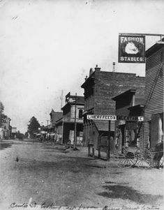 View of 200 block of West Center Street, Anaheim, CA, looking east; image shows south side of the street, with the Fashion Stables, established                          by Lafayette Lewis in 1872 at far right, next to the Anaheim and Wilmington Stage Office; large brick building in center of image is the old Langenberger building; the next structure, at the corner of Lemon and Center Streets, is the Commercial Hotel, showing the corner of the two-story wood-frame hotel with balcony.
