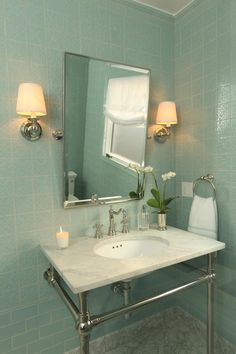 The white marble top and chrome legs of the console sink make a strong statement when combined with the ornately detailed light green tiles in this beach-inspired bathroom.