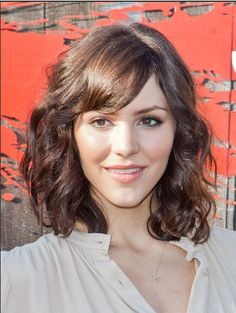If you want to try bangs with curly hair, take a cue from Katharine McPhee. This swept-to-the-side style works well.