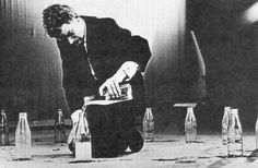 FLUXUS Tomas Schmit, Cycle for Water Buckets (or Bottles), 1959.  el artista, rodeado por un anillo de botellas de cristal, vierte agua de una botella a otra hasta que el agua se evapore o derrame.