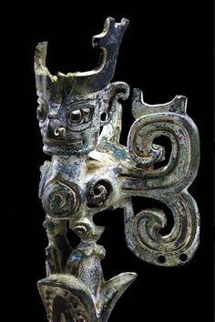 """Bird with Human Head  Sanxingdui Museum  """"This small (12cm, 4.7in) chimera once stood on the flower of a tree. The double-scroll piece on the right is a wing, and conjecturally restoring a similar missing piece on the left, we get something that looks amazingly like a butterfly."""""""