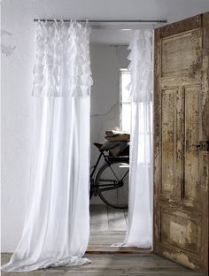 Beautiful distressed wood door contrasted with crisp white lace voile curtains with ruffles