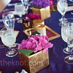 again, smaller centerpiece, maybe orange vases and candles, purple flowers (e.g. carnations?)