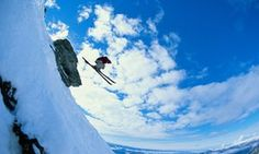 Male off-piste skier jumping off cliff, low angle view (fish eye)