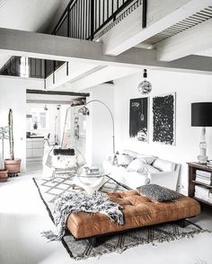 Bright white living space with a Morrocean area rug a leather daybed