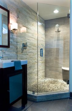 Frameless glass shower with river rock floor and stacked stone wall.