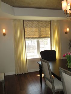 Roman shades coupled with drapes in dining room