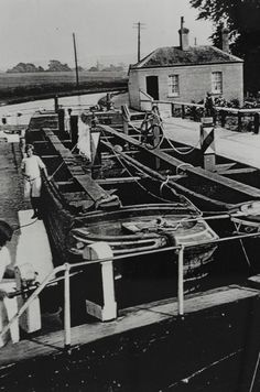 BW192-3-2-2-13-1-624 Pair of Grand Union Canal Company boats in a lock near Marsworth Description Black and white photograph showing the boats breasted up inside a lock, they are not loaded and have washing hung over the hold. There are boat people visible including one working the paddle gear in the foreground. There is a lock-keepers cottage in the background. Date 1930s