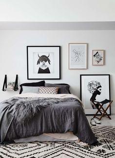 chambre taupe décorée d'une literie gris graphite, un tapis à motifs noirs et blancs et images en noir et blanc
