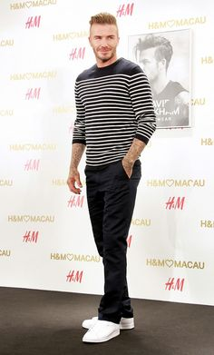 David Beckham wears a striped long-sleeve t-shirt, black jeans, and Adidas sneakers