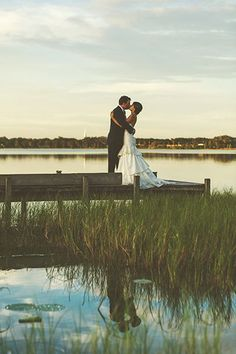 Sweet outdoor wedding photo of the bride and groom kissing on a dock