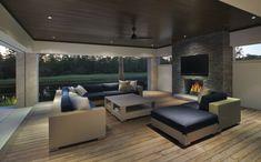 Terrasse couverte à part avec cheminée et salon pour la télé de cette maison de vacances