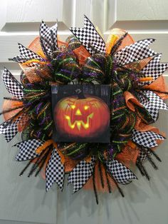 Nothing says Halloween like a flickering Jack-O'-Lantern. A square canvas is center stage in this multi-striped deco mesh wreath with orange paper ruffles. It is accented with black/white check rib Holidays Halloween, Halloween Crafts, Halloween Decorations, Halloween Stuff, Halloween Ideas, Halloween Tricks, Fall Decorations, Halloween Party, Wreaths And Garlands