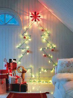 Com pisca-pisca, fita adesiva, fotos e outros materiais dá para montar uma árvore de Natal na parede e economizar espaço.
