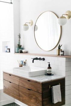 Floating Vanity and Sink Faucet | wooden vanity | white tile | Brass sconce | circular mirror | black faucet