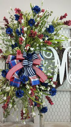 This wreath just screams American Pride. What a Patriotic and beautiful way to honor your country!! This wreath is filled with beautiful flowers in all the colors of our nations flag. This is a very large wreath. If you would like your monogram in red or blue just leave