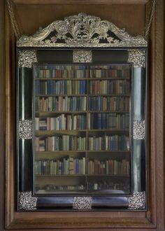 Books reflected in a mirror in the library sitting room, called the Big Room, at Sissinghurst Castle
