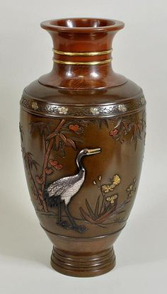 """Large Japanese mixed metal inlaid bronze vase, 19th century, neck with gold banding, body with silver and gold cranes, iris and butterflies amid bamboo. 14"""" high, 6 3/4"""" wide."""