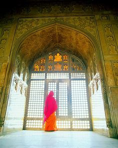 indian woman looking out a window in Shah Jahan's suite at the Agra Fort, Agra, India