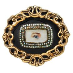 """Eye"" Brooch, England, Circa 1820  Hand painted ""eye"" brooch surrounded by a double row of natural pearls. Reticulated 18k gold and black enamel setting, with attached orignal safety."