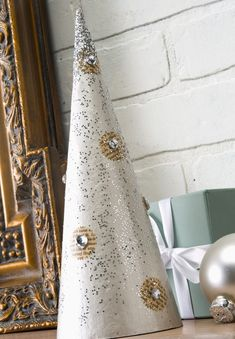 Spray paint cones with silver or gold and sprinkle with glitter while they are still wet.  Once they are dry, add embellishments like sticker rhinestones.