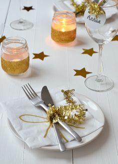 Tafeldek inspiratie. Ik gebruikte een gouden kerstslinger om het bestek vast te binden. Deze kerstslinger heb ik ook gebruikt om de naamkaartjes mee te decoreren. De waxinelichthouders heb ik zelf gemaakt. Dit is heel simpel! Neem twee (of meer) glazen potjes, beplak de potjes met twee repen dubbelzijdig tape, strooi vervolgens losse glitter over de tape en klaar zijn ze. De gouden sterren en servetten zijn van de Hema. De glitters en kerstslingers zijn van de Action.