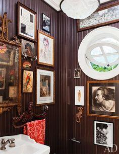 round window, antique mirror, art filled powder room
