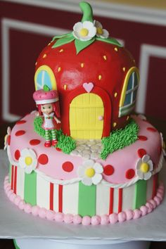 "Strawberry shortcake - The strawberry house was made with three 6"" rounds, carved and iced in buttercream with fondant accents- strawberry cake of course!  Strawberry shortcake doll is a toy."