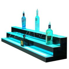 """Lighted Liquor Bottle Display 5 Step 72"""" by Led Baseline Inc. $993.00. These lighted bottle shelves feature a thin first level shelf and a taller second shelf that gives great bottle label exposure and allows for easy placement and removal.   Construction These units are built to suit your needs, simply select the width option that fits your bar Dimensions: 21"""" tall x 21.75"""" deep x 72"""" Semi-gloss black finish and impact, scratch resistant acrylic topLED specs Remote Control..."""