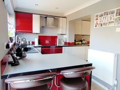 Red kitchen with red gloss cabinets, combined with white and grey and a red splashback for the cooker. Click to read out blog post about 3 red kitchens, all designed by Premier Kitchens in 2016. http://www.premier-kitchens.co.uk/Design-Inspiration/Premier-Blog/case-studies/3-red-kitchens-3-different-ways-all-from-premier-kitchens